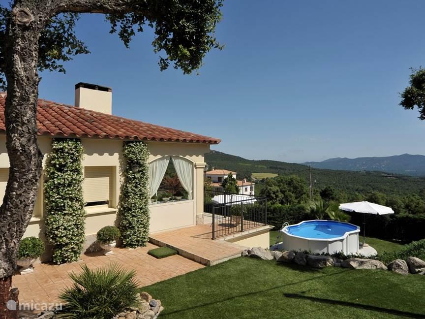 Villa Mas Caliu, met het zwembad, het uitzicht over de heuvels, en in de verte de zee.