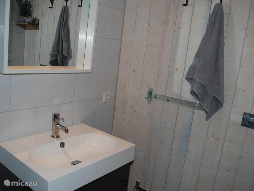 Comfortabele badkamer met vloerverwarming, handdoekradiator, badkamermeubel en douche.