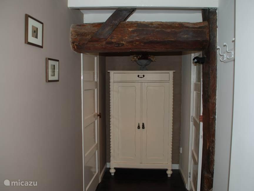 Hal 1: rechts naar slaapkamer 2, links naar hal 2. Het oude gebinte van de boerderij is in zicht.