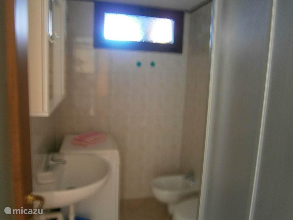 badkamer met bidet, douchcabine, toiletkast en wasmachine