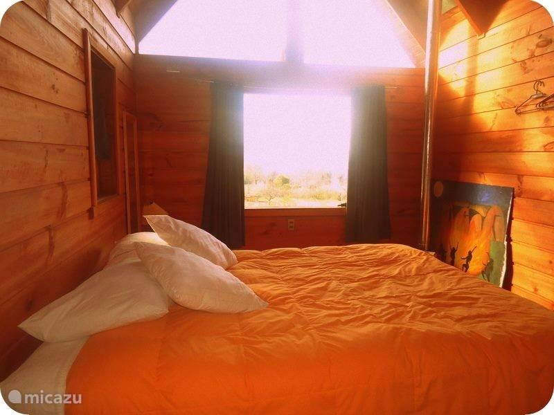 De slaapkamer met een ruim 2 persoonsbed en met houtkacheltje