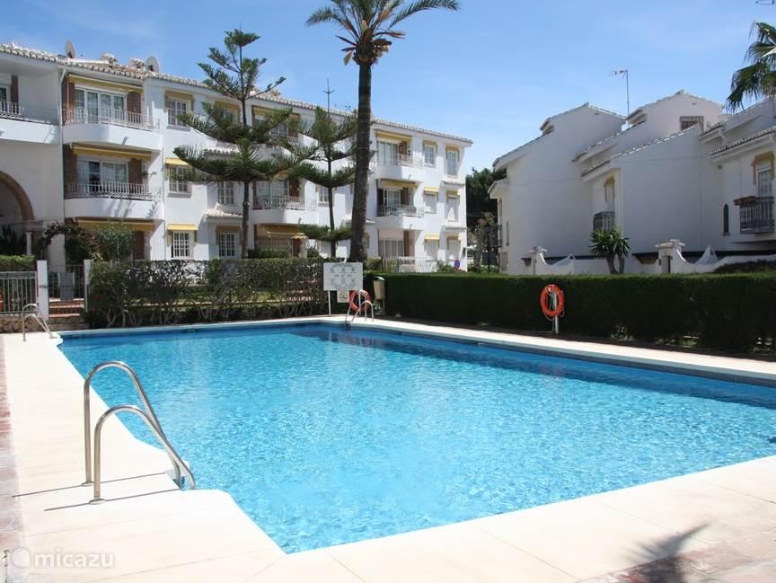 Zwembad met op de achtergrond uitzicht op ons appartement. Gelegen in een prachtige tuin, direct aan zee
