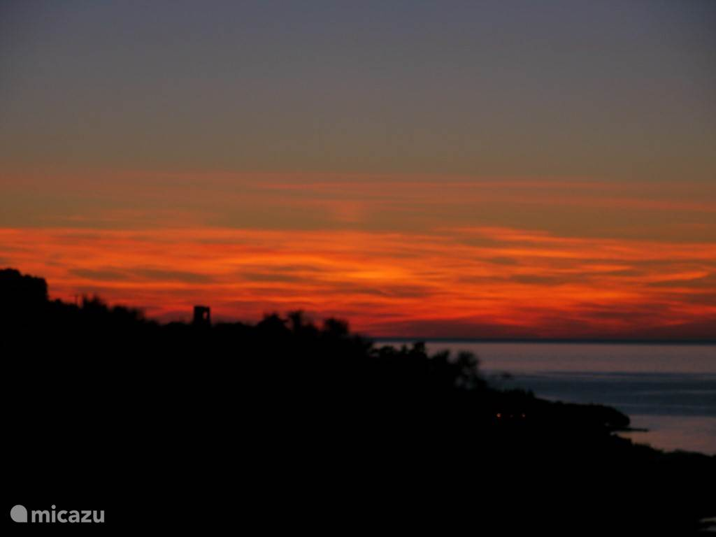 sunset with the Genoese tower and the sea and mountain from the garden