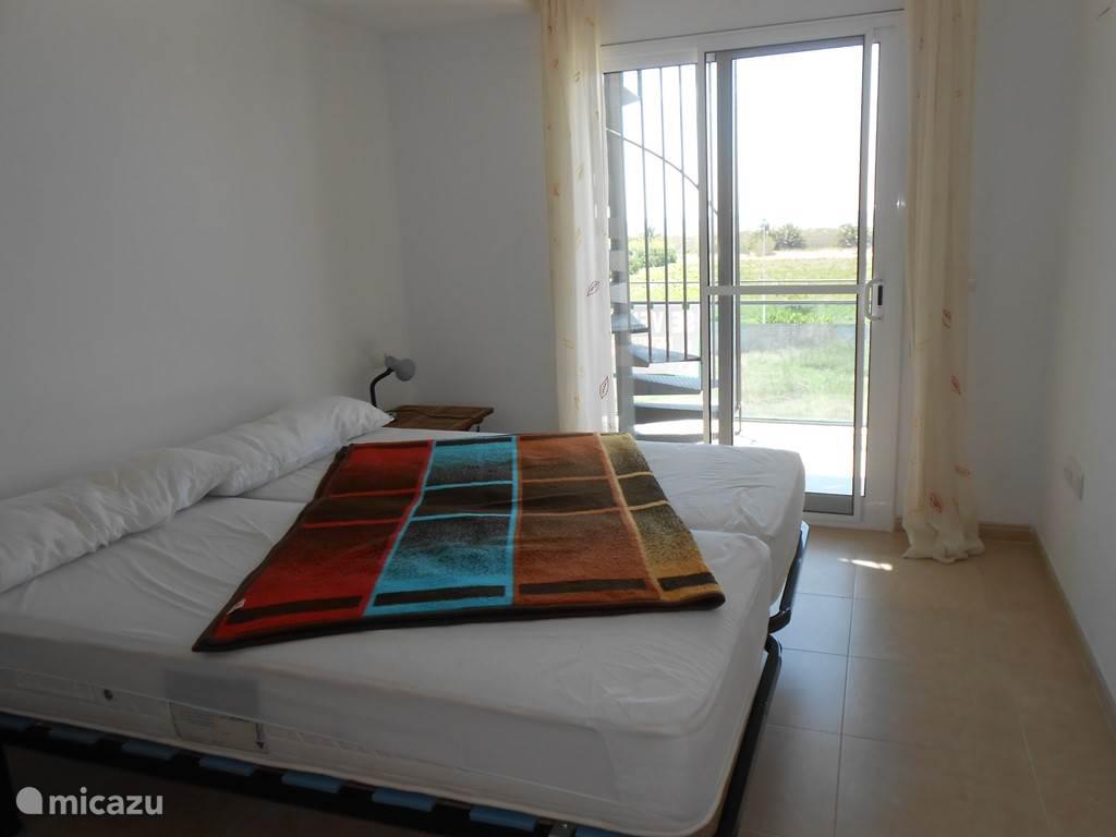 Slaapkamer met toegang naar het balkon .