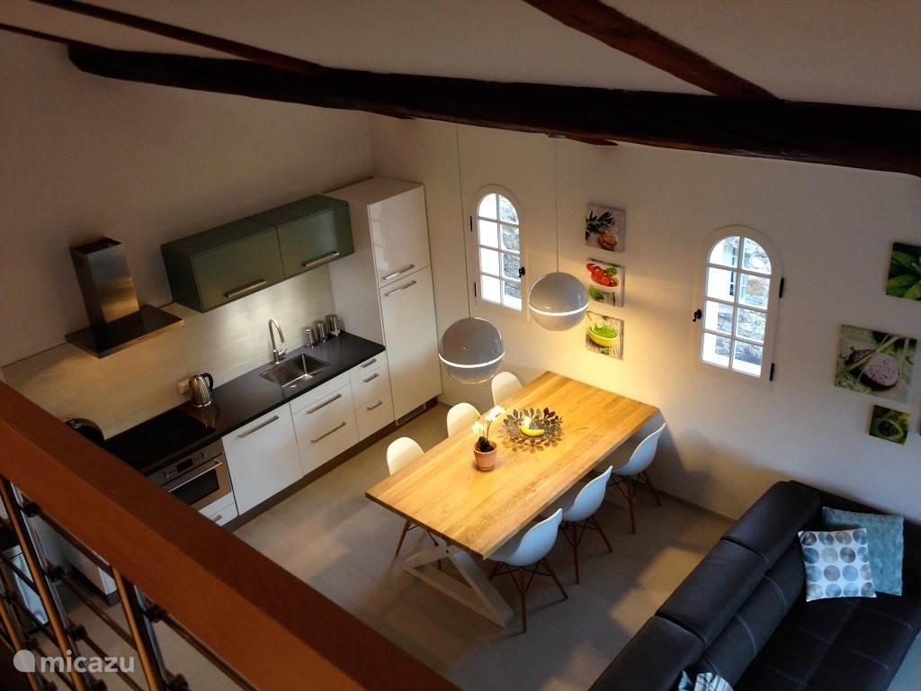 Luxe keuken, eettafel, grote bank, tv en balkon
