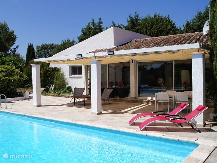 with large pool and surrounding terrace with lounge chairs for sun