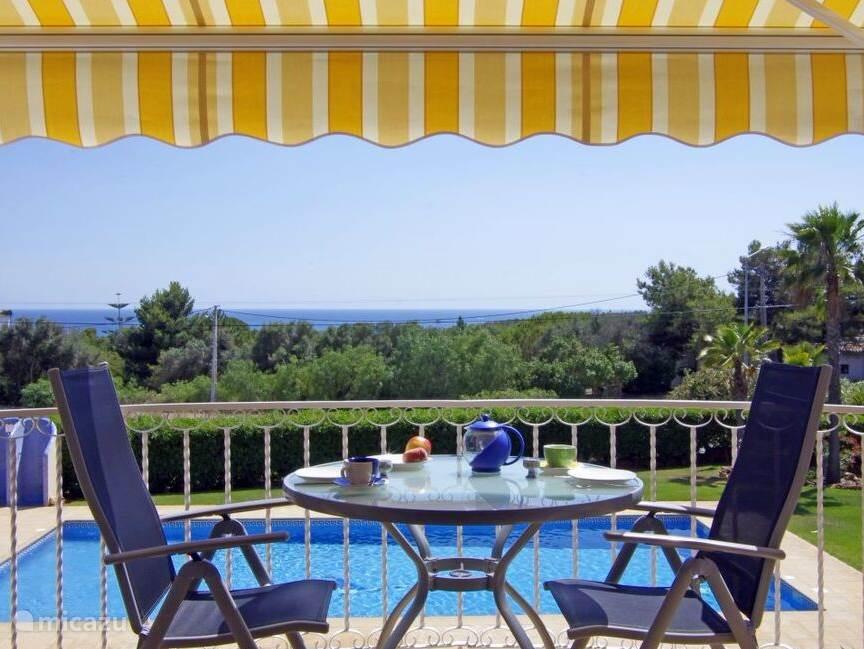 genieten van het geweldige uitzicht. Balkon met tafel en vier gemakkelijke stoelen en zonnescherm..