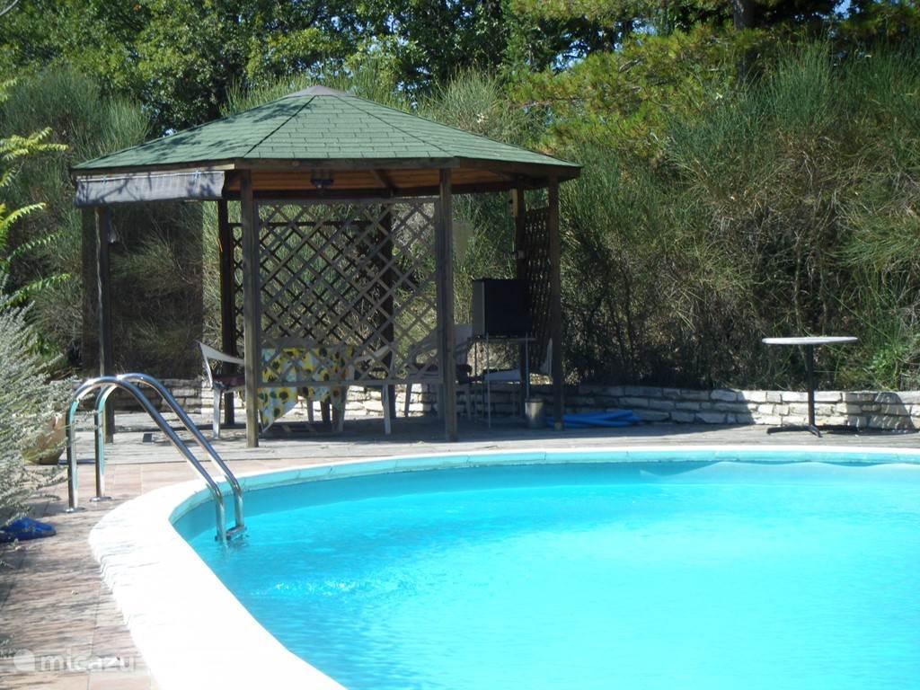 het prieel bij het zwembad en de stenen barbecue, voorzien van eettafel en -stoelen en koelkastje