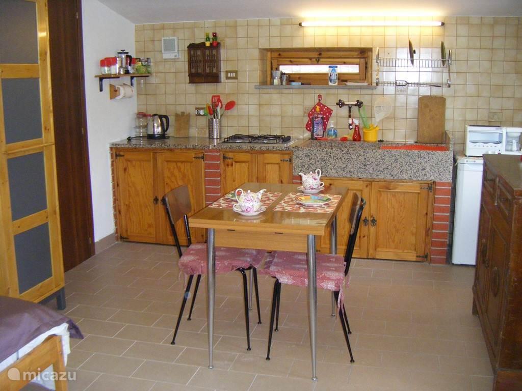 Keuken met kookgelegenheid, koelkast, oventje en eettafel