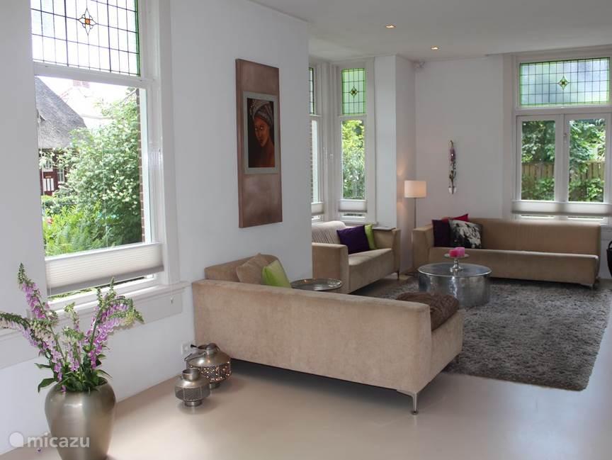 Ruime lichte woonkamer met open haard, flatscreen tv en vloerverwarming.
