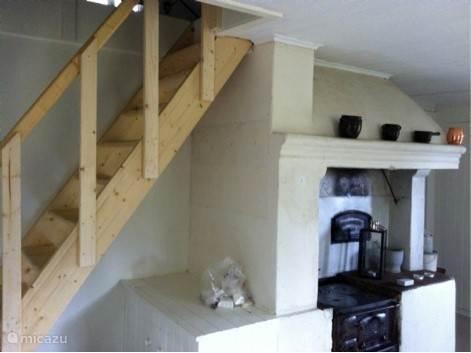 Keuken met 19e eeuwse fornuis en houten trap naar bovenverdieping.