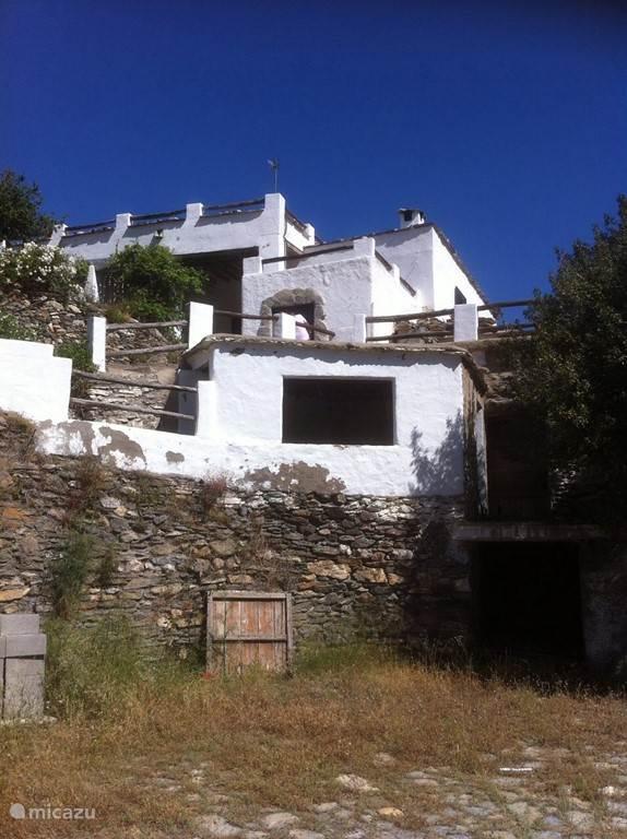 Het huis vanaf de oude graancirkel waar het graan gedorst werd. Via een pad en aansluitend een trap loop je langs bloeiende geraniums omhoog naar het huis.