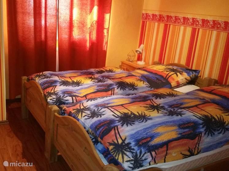 Slaapkamer met twee bedden en een kledingkast