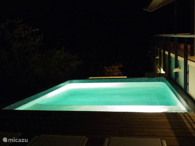 De mysterieuze sfeer van het verlichte zwembad.