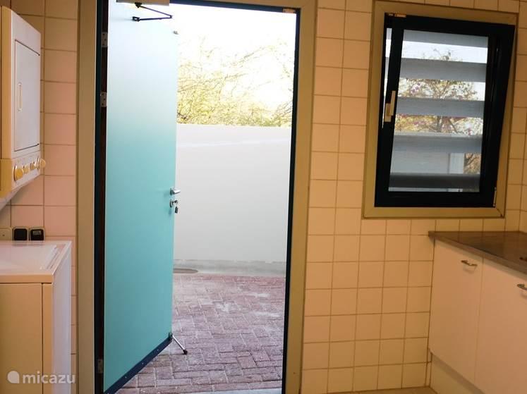 De wasruimte met wasmachine, droger, spoelgelegenheid en toegang tot de (buiten) droogruimte.