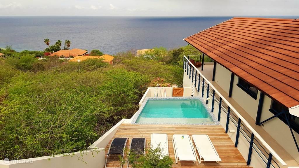 De vrije ligging van het zwembad met zicht op zee.