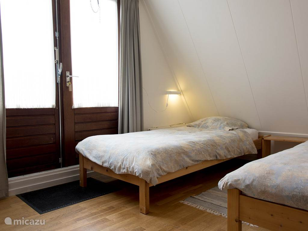 Slaapkamer met een groot balkon.