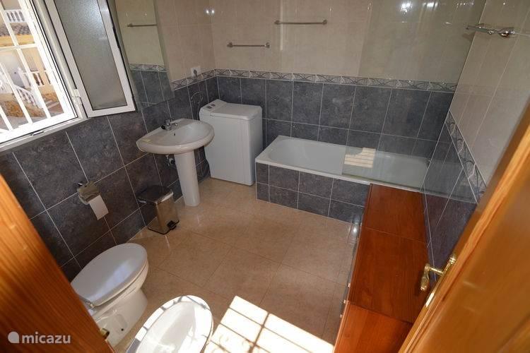 De grote badkamer bevindt zich op de etage. Naast ligbad met douche, bidet en wc is hier ook een wasmachine geplaatst.