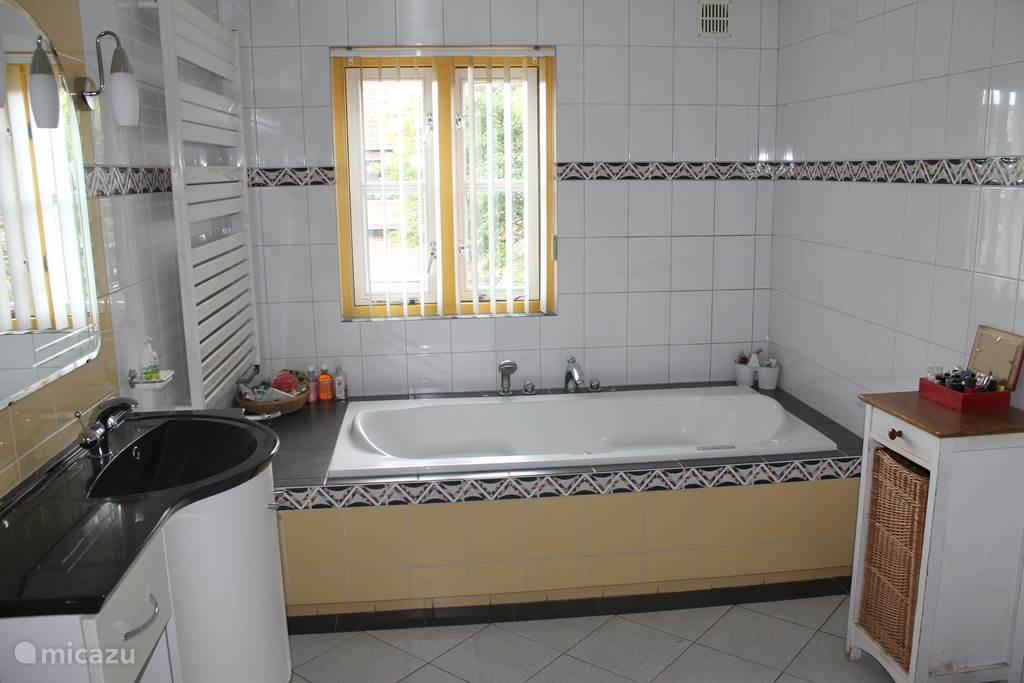 Badkamer met bad en douchecabine.