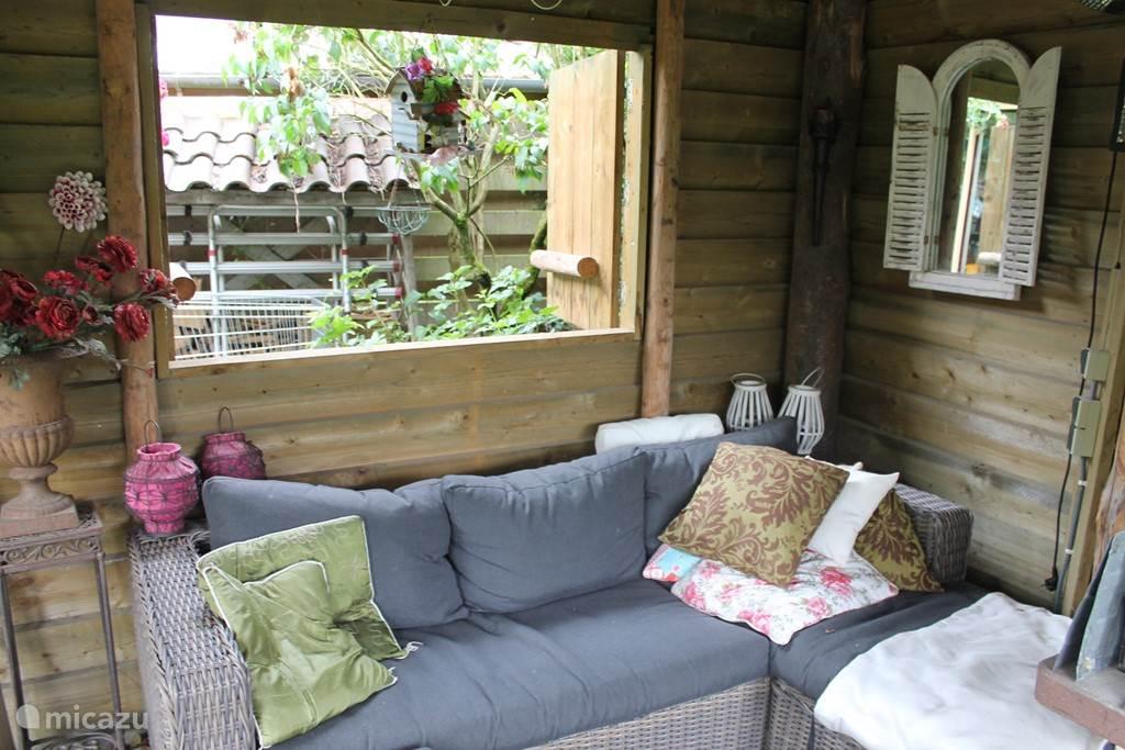 Loungebank in veranda met doorkijkje.