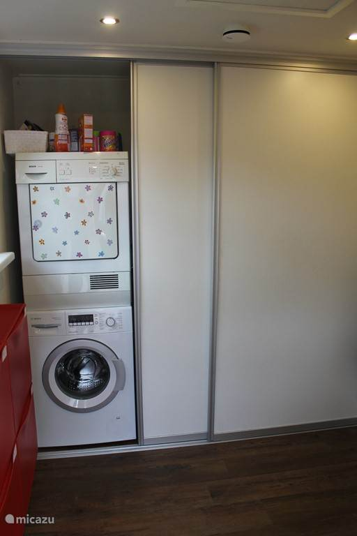 Bijkeuken met kastruimtes, wasmachine en wasdroger.