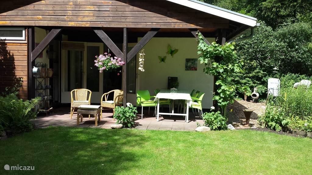 De voorkant van het huisje heeft een overdekt terras met voordeur en openslaande tuindeuren naar de woonkamer. Aan deze kant bevindt zich ook de fijne tuin.