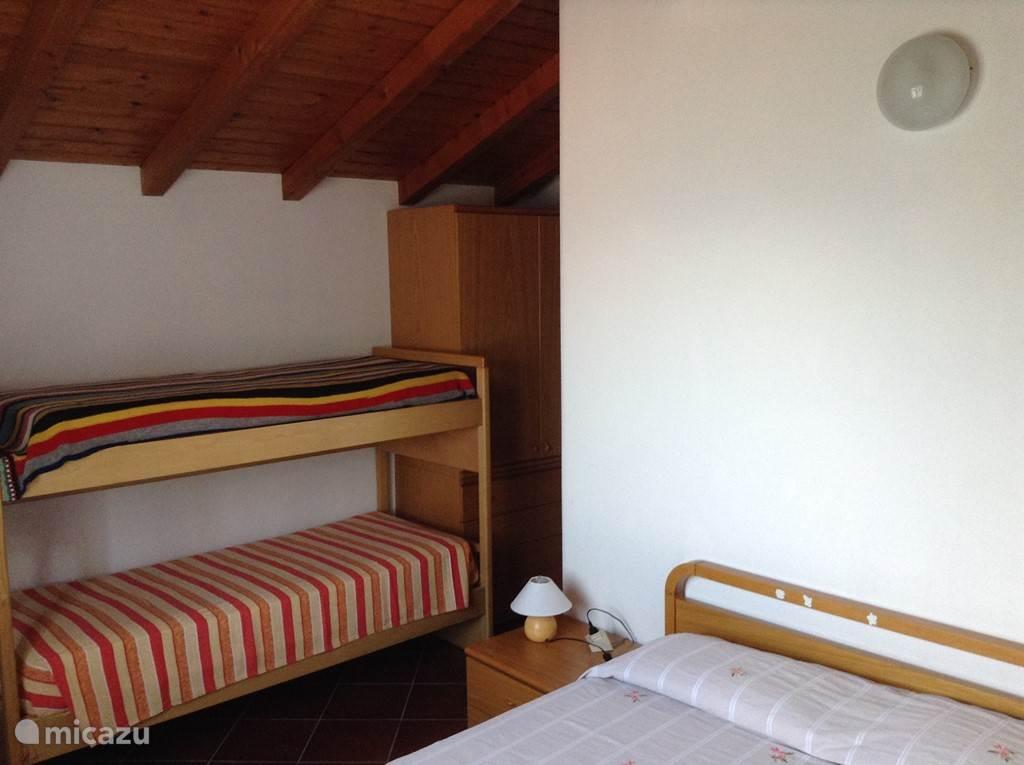 slaapkamer met tweepersoonsbed en stapelbed