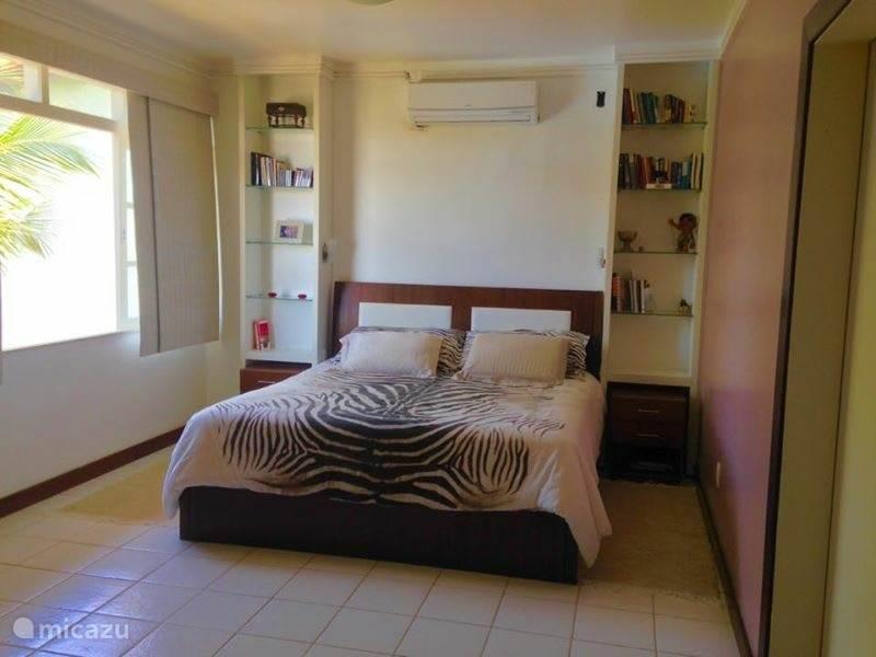 Op de eerste verdieping bevindt zich de grote slaapkamer. Deze is voorzien van een groot tweepersoonsbed, airco en veel kastruimte. De grote slaapkamer heeft een doorgang naar de privé badkamer.