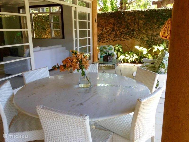 The beautiful and charming veranda is equipped with a large dining table. During breakfast can be enjoyed from the finest bird sounds. From the dining table you have a beautiful view of the garden and pool.