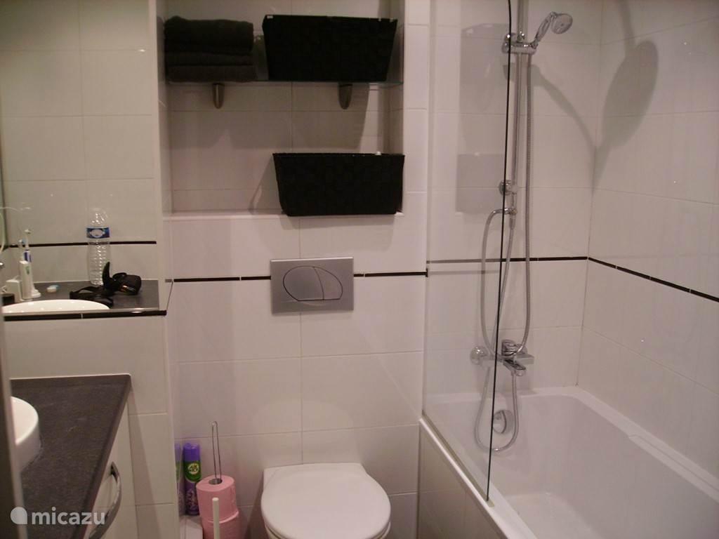 De moderne badkamer waar u door de stortdouche ook comfortabel kunt douchen. In het badmeubel staat de wasmachine