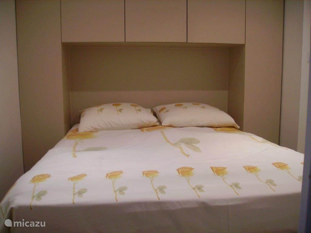 De slaapkamer met boxspring en kastruimte