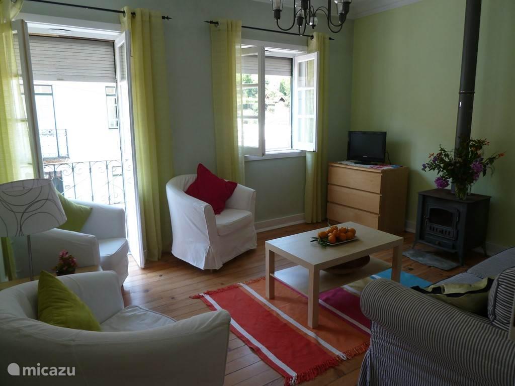 De woonkamer met openslaande deuren aan de voorkant en een slaapbank.
