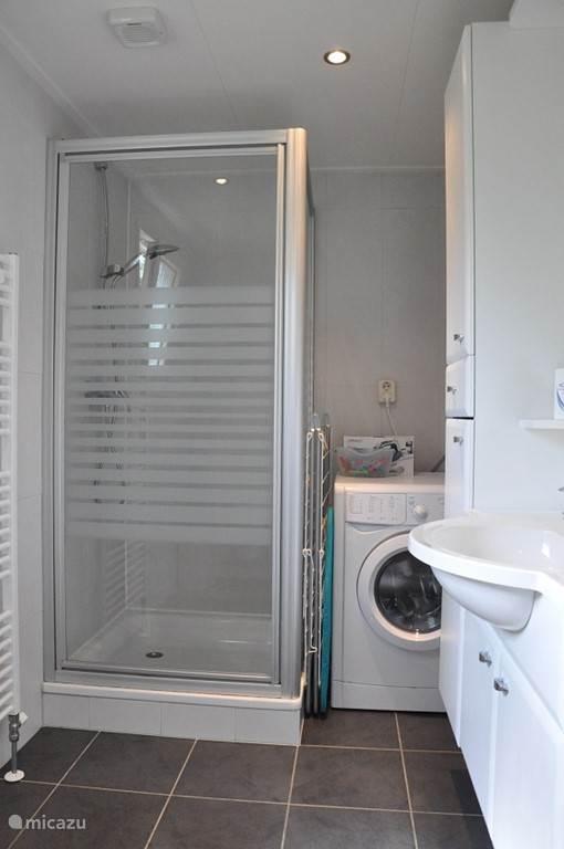 Luxe badkamer met douche, wc, wastafel, wasmachine, droogrek en strijkplank met strijkijzer
