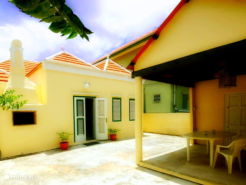 Achter Porch en Hoofdingang (via achter deur) Links is een BBQ en rechts zijn de 2 ramen van badkamer #2. Er zijn tuinstoelen en een wasmachine voor gemeenschappelijk gebruik. Men kan hier het beste in de ochtend of avond zitten.