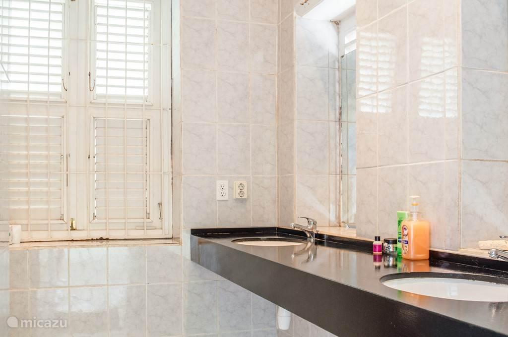 Badkamer #2 Sluit aan op de achter-porch (spiegels zijn voor de ramen geplaatst). Deze badkamer is identiek aan de eerste badkamer. Het is van de binnenkant afsluitbaar en voor gemeenschappelijk gebruik.