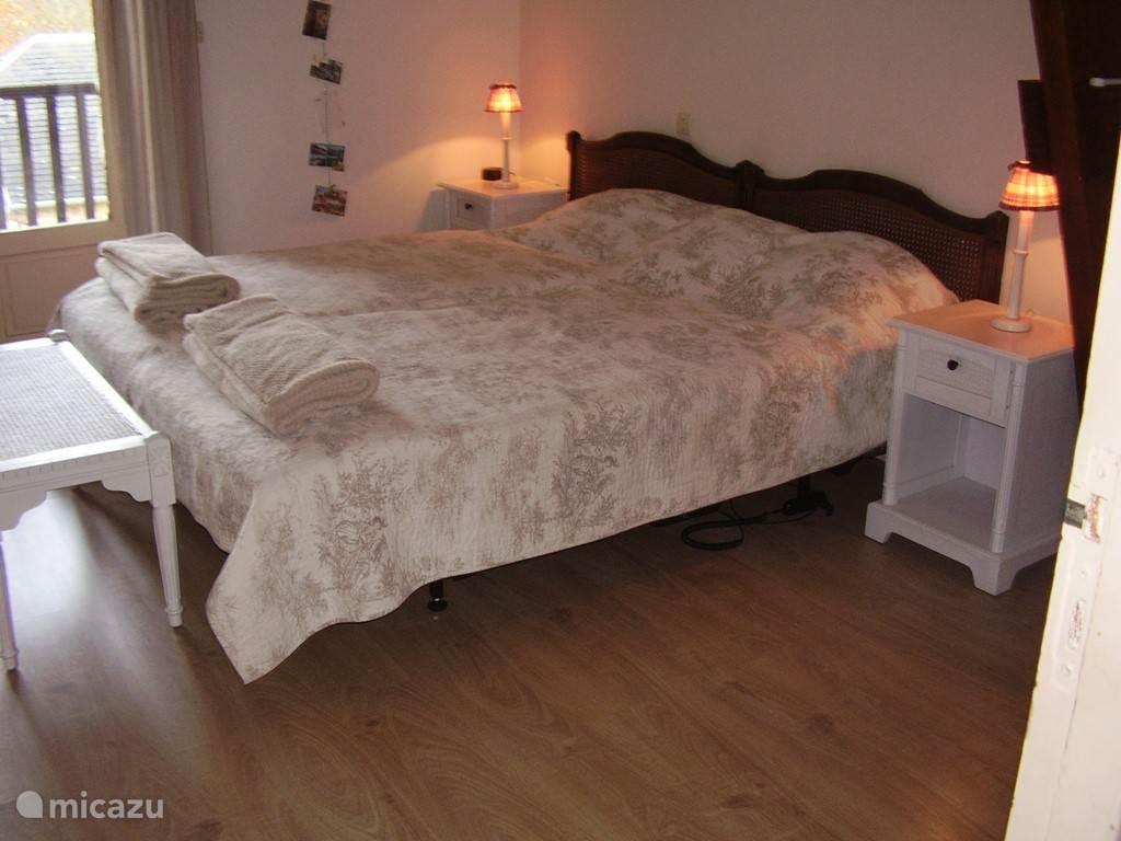 Slaapkamer met luxe, elektrisch verstelbare bedden en een royaal balkon.