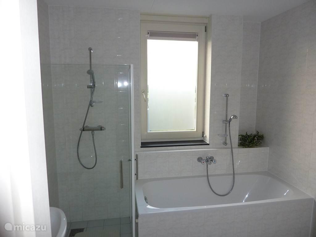 Badkamer met ligbad, douche, extra toilet en vloerverwarming.