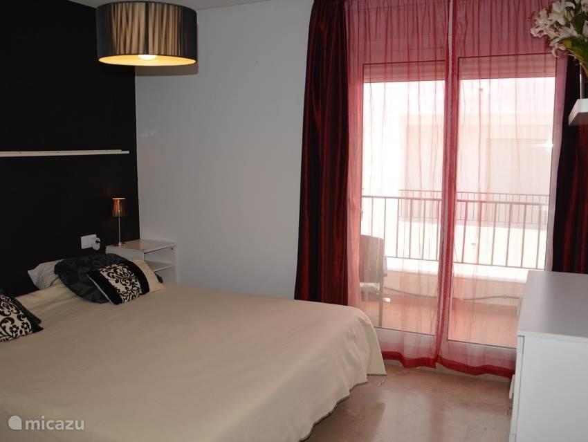 hoofd slaapkamer met 2 persoons bed van 210 cm x 180 cm en toegang tot een eigen balkon van 5 m2 met zee zicht