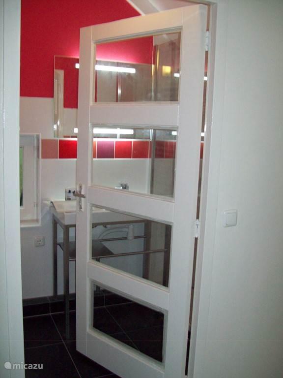 De tweede badkamer, met inloopdouche, toilet (met prachtig uitzicht!!), wastafelmeubel en design radiator, op de tweede etage