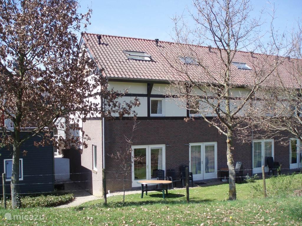 De zijkant en achterkant van het huis; inmiddels is er een mooi terras gekomen met haagjes tussen de huizen