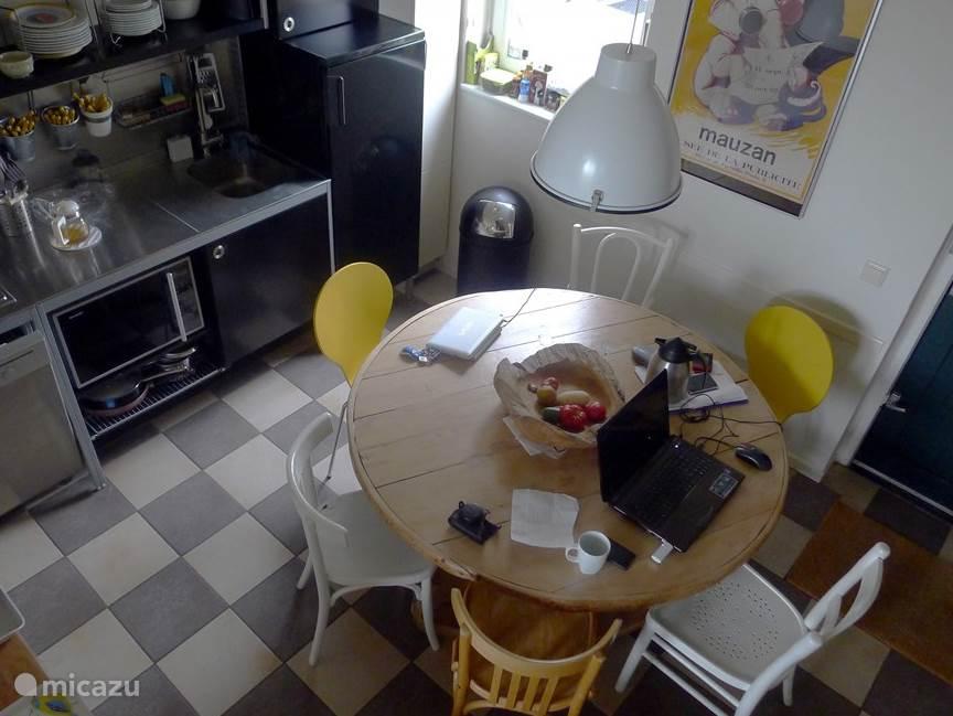 De eetkeuken, inclusief grote koelkast, vaatwasser, combi magnetron en grote rond antieke Zwitserse tafel