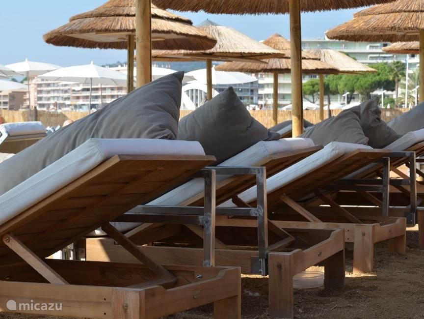 Ligbedden en parasols op het strand