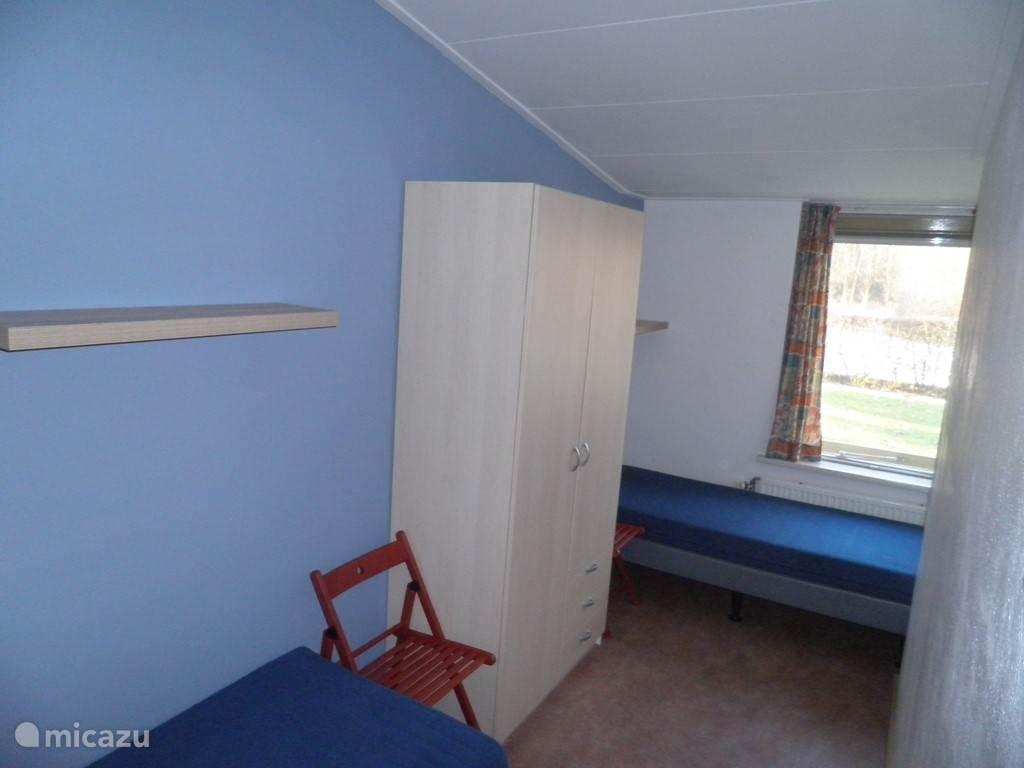 Slaapkamer met twee losse bedden. In de andere vakantiewoning staat een stapelbed met een los bed, overnachting voor vijf personen