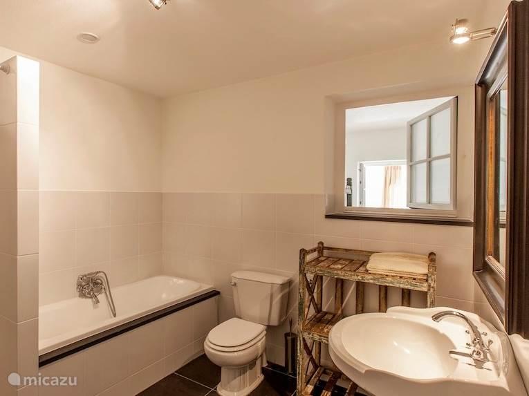 Badkamer met bad, aparte douche, toilet, wasmachine en droger