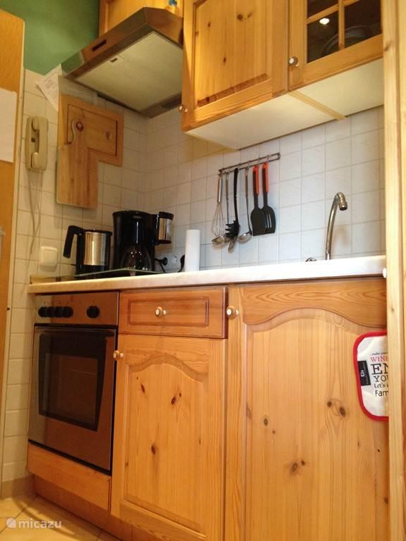 Küche mit Kaffeemaschine, Backofen, Herd, Mikrowelle und Wasserkocher