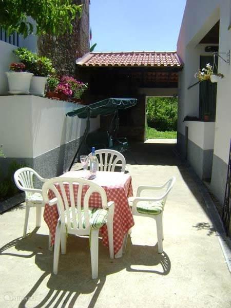 Het kleine terras bij de BBQ en de broodoven met zicht op de tuin.