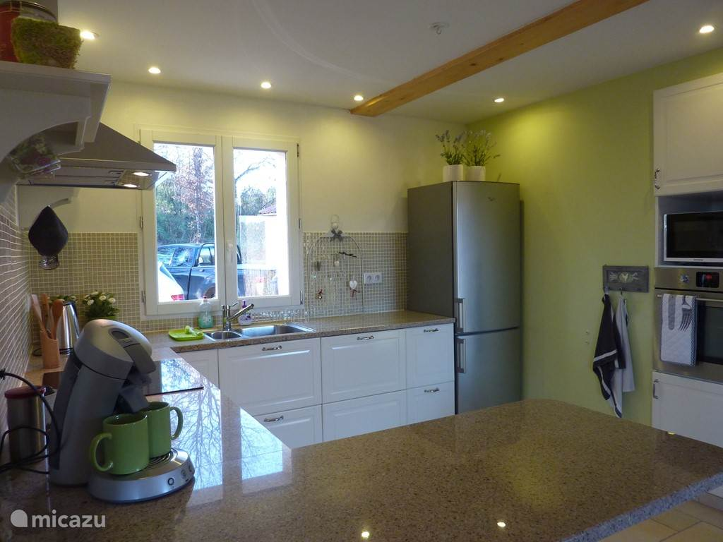 kitchen with breakfast bar. The kitchen has an electric oven, microwave, fridge-freezer, 4 gas induction hob with extractor fan and kitchen utensils.