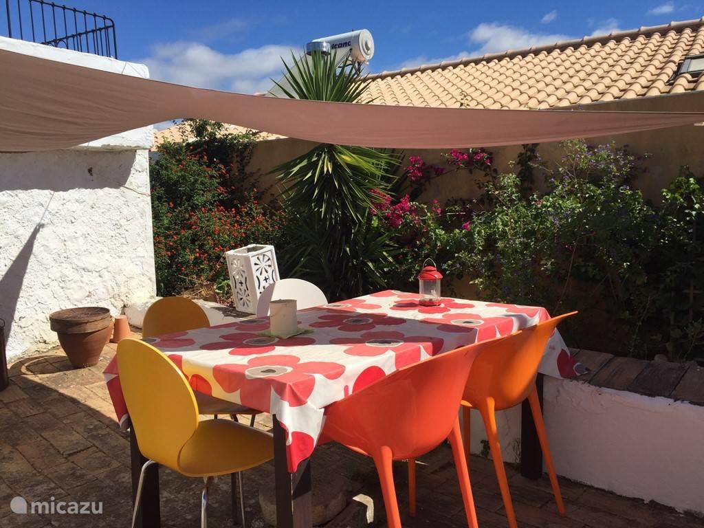 Gedeelte van de tuin met eettafel en 5 stoelen, Zonnedoek , boven de witte muur is het dakterras met daybed en 2 stoeltjes en tafeltje met prachtig uitzicht over de natuur, bergen en dorp.