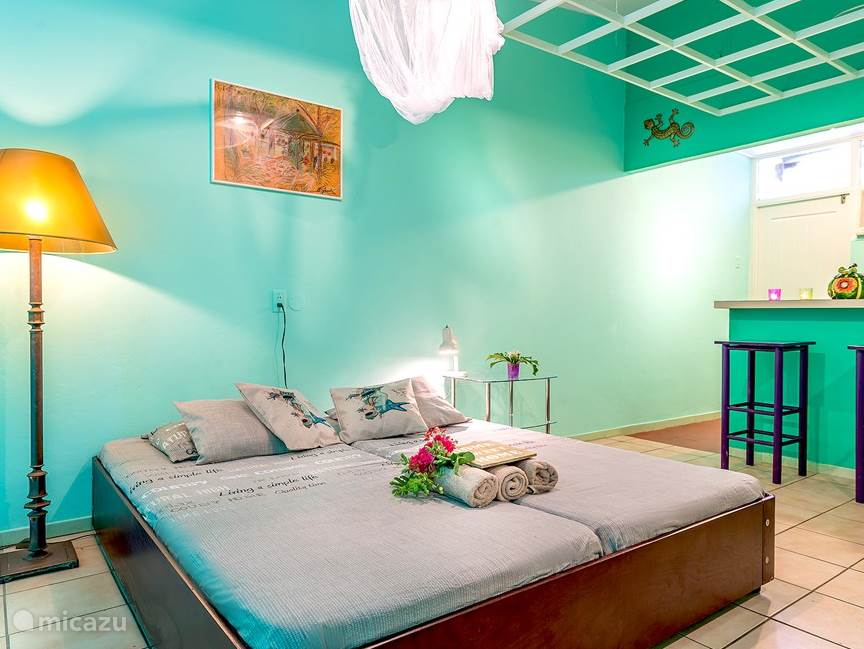 The colorful apartment has a kitchenette, with open bar and bar stools, a sleeping area, a sitting area, ample storage space, a bathroom and a covered terrace.