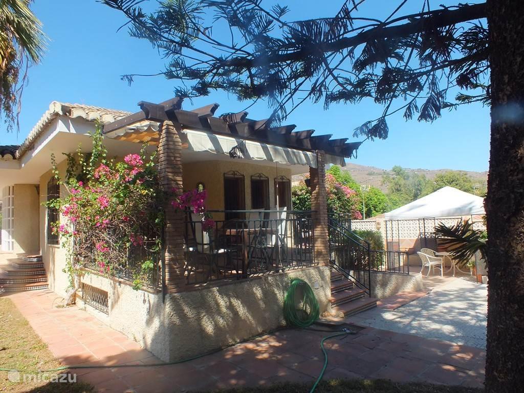 Zijkant van het huis, met groot terras, zij terras, en meerdere zitjes bij het huis en naast het zwembad